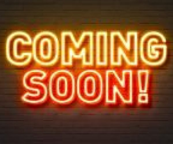 Coming soon neon sign on brick wall background